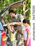 Family with car in nature - stock photo