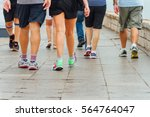 Stock photo several people walk down a sidewalk doing exercise 564764047