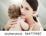 smiling mother holding her cute ... | Shutterstock . vector #564775987