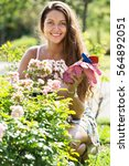 Stock photo positive smiling young woman gardening with roses in yard 564892051