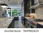 Stock photo modern kitchen with brown kitchen cabinets oversized kitchen island granite countertops 564982624