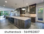 Stock photo modern kitchen with brown kitchen cabinets oversized kitchen island with bar stools granite 564982807