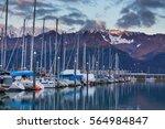 Boats at a pier in Seward with mountains in background. Seward