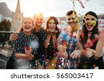 Stock photo group of friends enjoying party and throwing confetti friends having fun at rooftop party 565003417