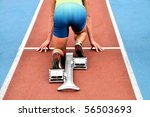 Starting runner in a starting block on an athletic track - stock photo