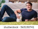 Stock photo young handsome man playing with white kitten 565150741
