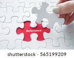 Small photo of Close up of girl's hand placing the last jigsaw puzzle piece with word Reference
