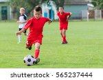 boy kicking soccer ball on... | Shutterstock . vector #565237444