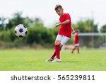 Boy Kicking Soccer Ball On...