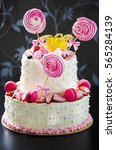 Small photo of Large white and pink two-tier cake for girl with fondant crown.