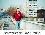 man in red hoodie jogging... | Shutterstock . vector #565429885