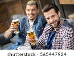 happy male friends drinking... | Shutterstock . vector #565447924