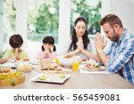 family praying while sitting at ... | Shutterstock . vector #565459081