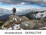 hiker standing on a rock.... | Shutterstock . vector #565461745