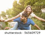 happy man carrying woman on... | Shutterstock . vector #565609729