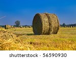 Hay Bale In Field With A Blue...
