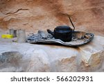 Small photo of Burned tea kettle, glass, and other utensils of a nomadic cave dweller, bedouin in Petra Jordan Antique city featured in Indiana Jones