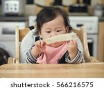 asian baby girl eating bread... | Shutterstock . vector #566216575