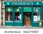 Small photo of Wick, Scotland - June 4, 2012: Closeup of the green painted storefront of Wick Pharmacy owned by Mr. Manson. Display of colorful packages in windows. Trashcan upfront.
