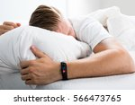 Small photo of Fitness Activity Tracker With Heartbeat Rate On Man's Hand Over Bed