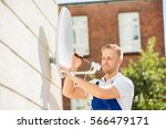 smiling young man installing tv ... | Shutterstock . vector #566479171