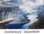 Trolltunga (Troll Tongue), climber standing at edge of cliff Trolltunga looking at rainbow against mountains, over amazing blue lake. Beautiful landscape of wild nature in Norway, Scandinavia.