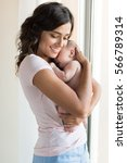 pretty woman holding a newborn... | Shutterstock . vector #566789314