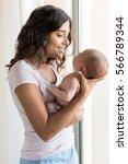 pretty woman holding a newborn... | Shutterstock . vector #566789344