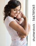 pretty woman holding a newborn... | Shutterstock . vector #566789365