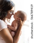 pretty woman holding a newborn... | Shutterstock . vector #566789419