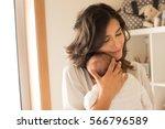 pretty woman holding a newborn... | Shutterstock . vector #566796589