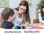 kindergarten teacher supports... | Shutterstock . vector #566981095