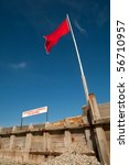 beach safety warning sign and flag against a clear blue sky - stock photo