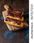 Small photo of Traditional French dessert. Eclair with chocolate icing. Dark background