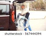 man loading wheelchair of... | Shutterstock . vector #567444394