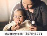 mother giving medicine to baby | Shutterstock . vector #567548731