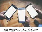 three hands holding smart phones | Shutterstock . vector #567685939