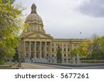 The Alberta Provincial Legislature Building and reflecting pond in fall under overcast sky.