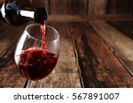 red wine in glass on wooden... | Shutterstock . vector #567891007
