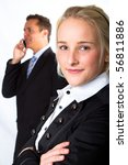 A young, confident, businesswoman with a businessman in the background - stock photo