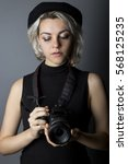 Small photo of Female professional or amateur photographer holding a dslr camera. This photographic gear is used by both self employed artists and journalists or for tourism and hobbies.