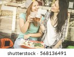 young women eating pizza and... | Shutterstock . vector #568136491