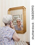 Elder Lady Pensive At The Mirror