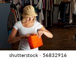 young woman searching her handbag in a boutique - stock photo