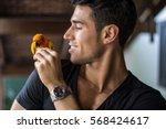 Stock photo smiling handsome man feeding parrot sitting on his shoulder horizontal indoors shot 568424617