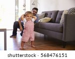 father watching baby daughter... | Shutterstock . vector #568476151