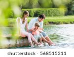 happy family sitting on jetty... | Shutterstock . vector #568515211