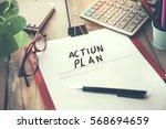 Small photo of action plan text on notebook with stationery on wooden desk
