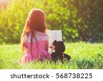 Little Girl Reading Book With...