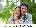 smiling couple embracing in... | Shutterstock . vector #568858444